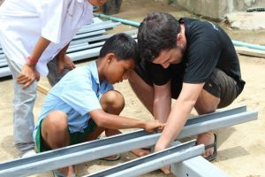Student from New Road helps Building Trust bolt frame together